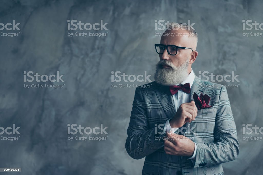 Portrait of virile handsome luxurious trendy stylish intelligent smart dreamy thoughtful macho brutal groomed sharp dressed cool classic millionaire fixing cufflinks isolated grey background copyspace stock photo