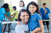 Cheerful volunteer nurse embraces elementary age female patient during free community health fair.