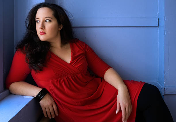 portrait of voluptuous woman wearing red dress and posing - curvy voluptuous women stock photos and pictures