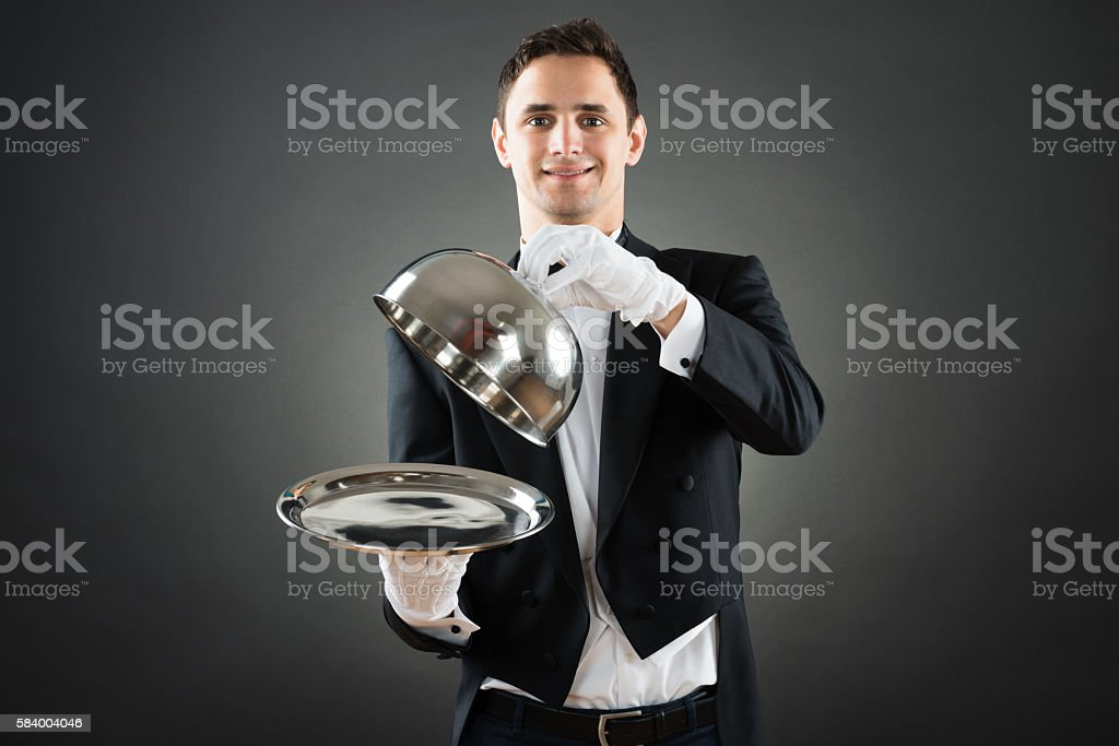 Portrait Of Waiter Holding Cloche Over Empty Tray stock photo