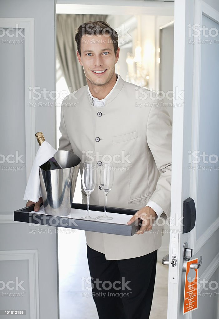 Portrait of waiter in hotel room doorway with tray of champagne and glasses stock photo
