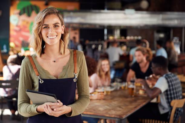 Retrato de mesera que sostiene menús sirviendo en el concurrido bar restaurante - foto de stock