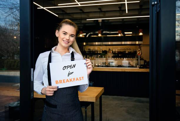 Portrait of waitress showing sign with open for breakfast at restaurant door stock photo