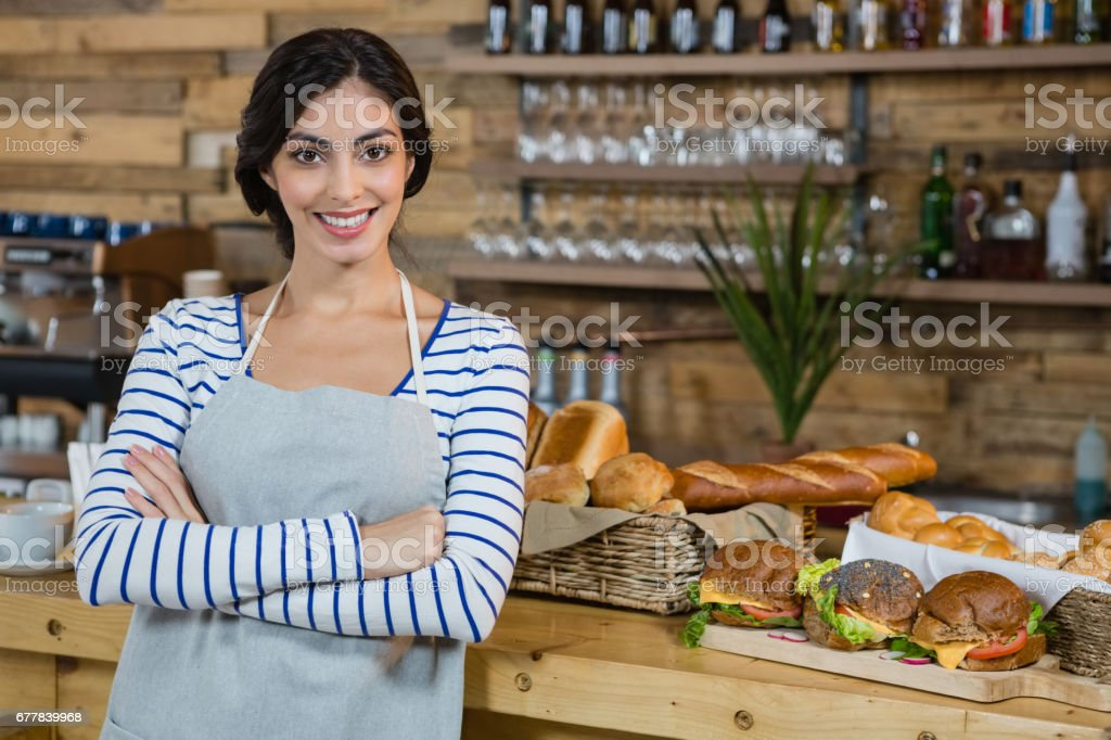 Portrait of waitress standing with arms crossed at counter royalty-free stock photo