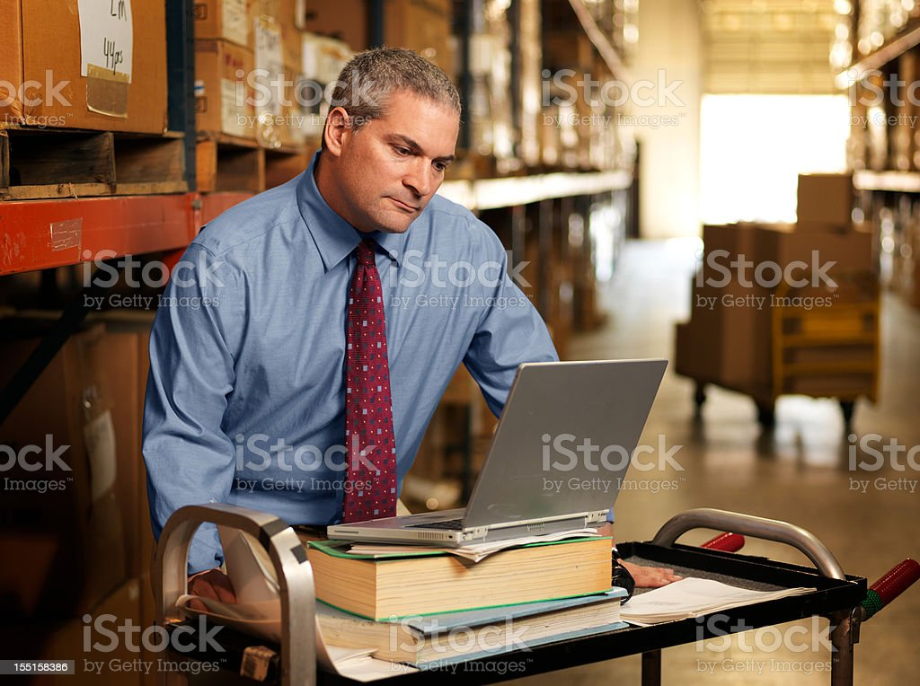 Portrait of Warehouse Businessman with Laptop royalty-free stock photo