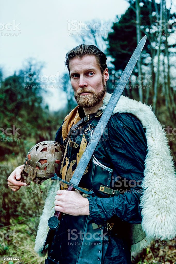 Portrait of warrior with beard who holds sword stock photo