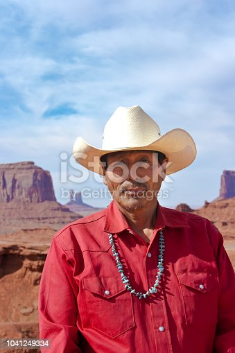 Portrait of a native American cowboy at the Monument Valley Tribal Park in Arizona, USA. A famous tourist destination in the southwest USA. The native American is a Navajo tribe native. Photographed on location.