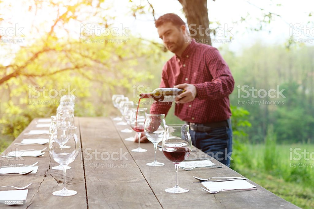 portrait of wine producer pouring red wine into wine glasses - foto stock
