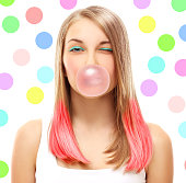 Portrait of winking happy girl with chewing gum