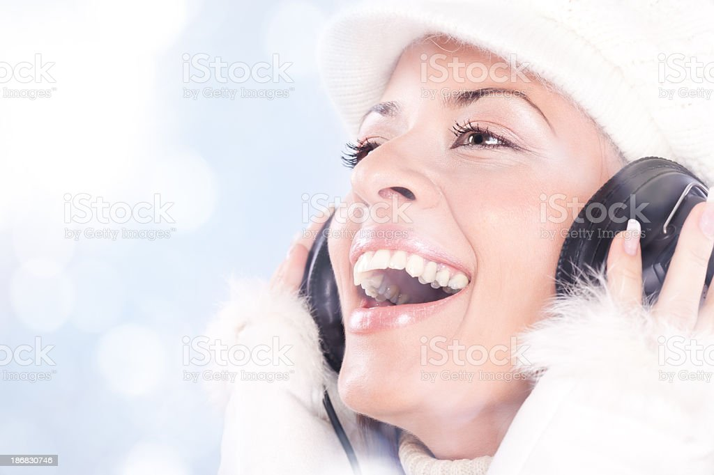 Portrait of winter beautiful woman with gloves, hat and headphones royalty-free stock photo