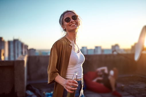 Woman dancing and holding bottle of beer at roof party.