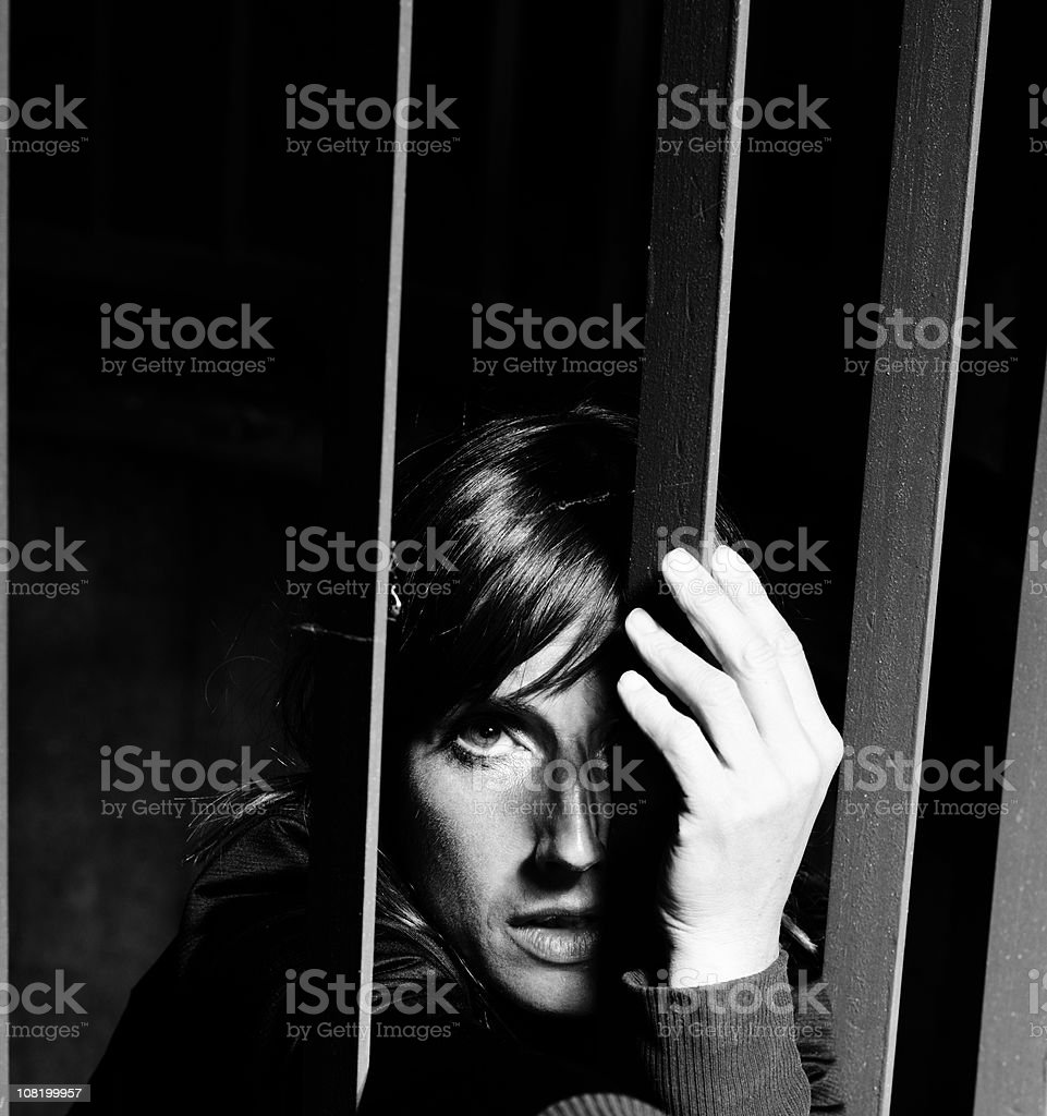 Portrait of Woman Behind Metal Bars, Black and White royalty-free stock photo