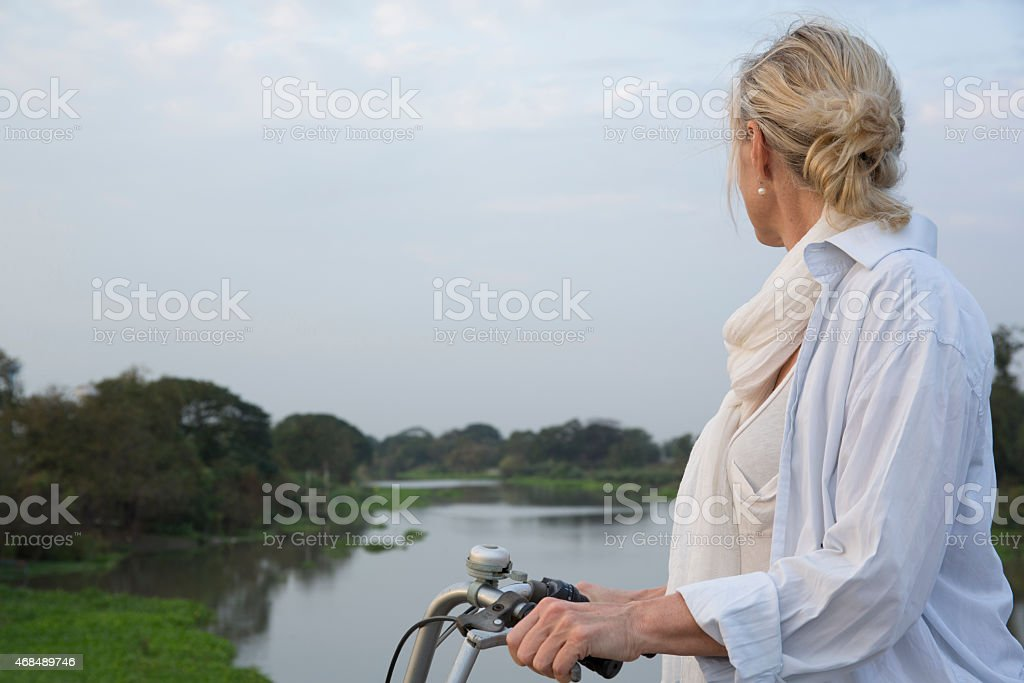 Portrait of woman biking over river stock photo