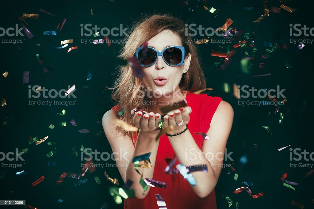 Portrait of woman blowing confetti stock photo