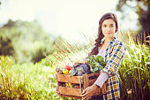 istock Portrait of woman carrying vegetables in crate at farm 588386824