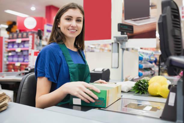 portrait of woman cashier smiling - icona supermercato foto e immagini stock