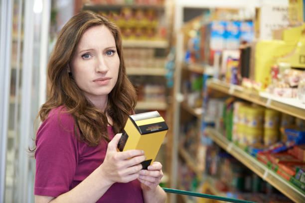 Retrato de mujer comprobando el etiquetado de alimentos en caja en el supermercado - foto de stock