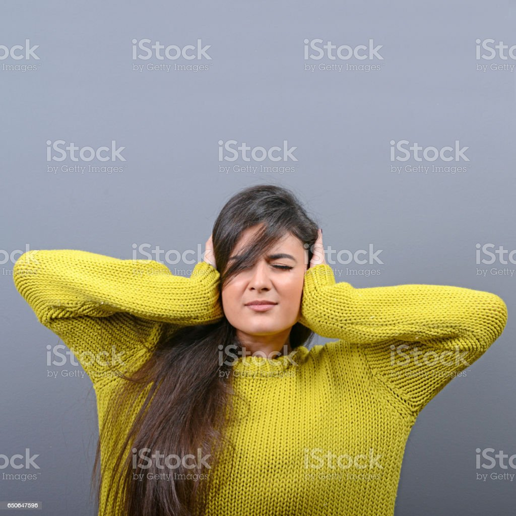 Portrait of woman covering ears with hands against gray background stock photo