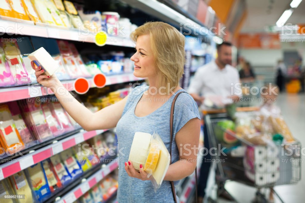 Portrait of woman holding assortment of cheese in grocery shop stock photo