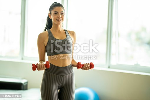 1035512048istockphoto Portrait of woman holding weights 1195776263