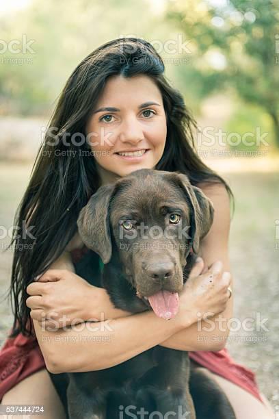 Portrait of woman hugging pet dog Portrait of loving owner hugging pet retriever Adult Stock Photo