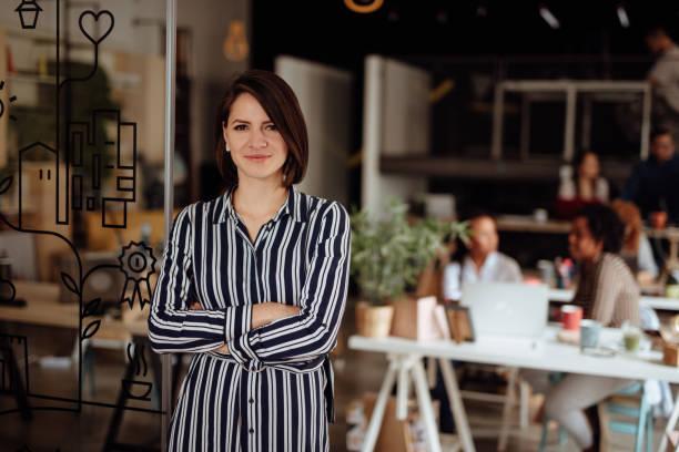 Porträt der Frau an einem geschäftigen modernen Arbeitsplatz – Foto