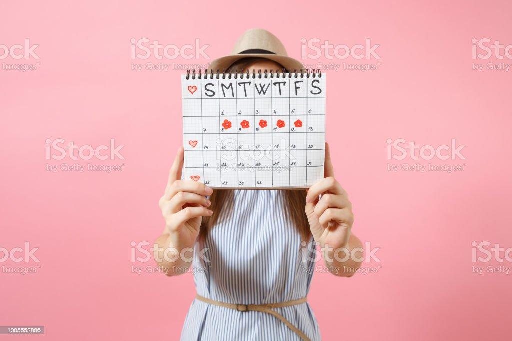 Portrait de femme en robe bleue couvrir le visage, se cachant derrière le calendrier des périodes de vérifier les jours de menstruation isolés sur fond rose tendance. Concept médical, soins de santé, gynécologique. Copiez l'espace. - Photo