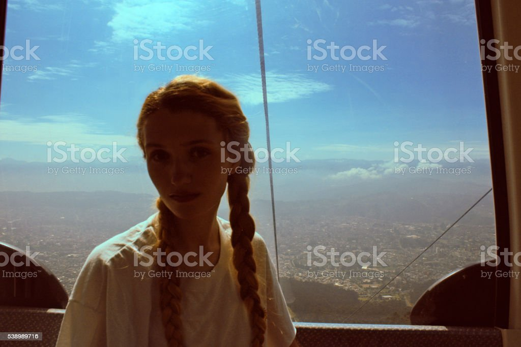 portrait of Woman in cable car with cityscape view, Ecuador stock photo
