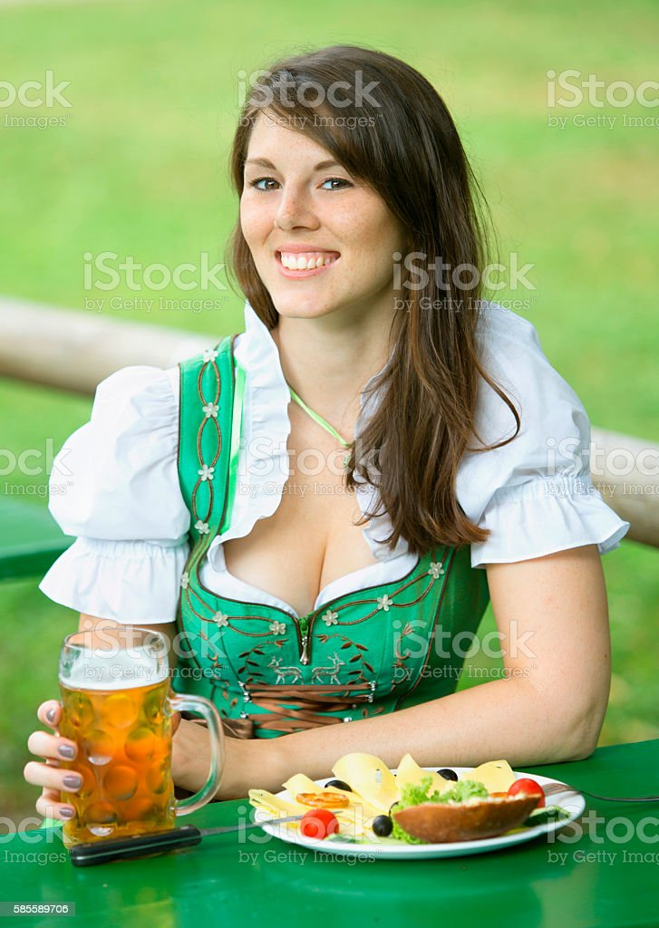 portrait of woman in dirndl with beer and food – Foto