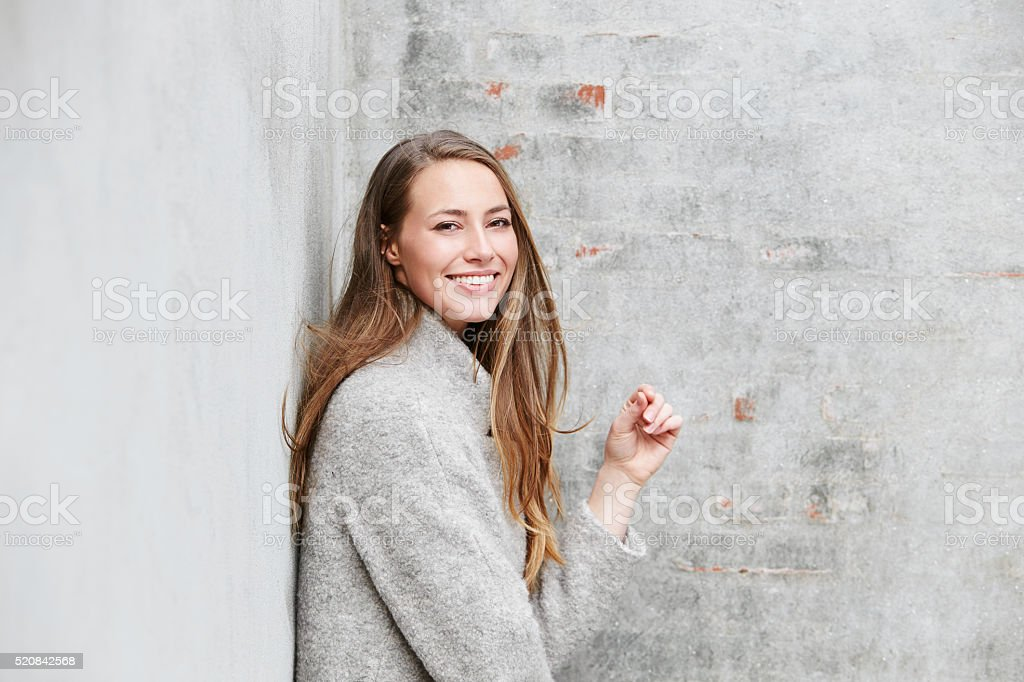 Portrait of woman in gray fashion against wall stock photo
