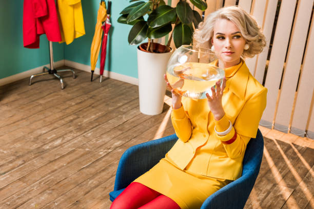 portrait of woman in retro clothing with golden fish in aquarium sitting on chair at colorful apartment, doll house concept stock photo