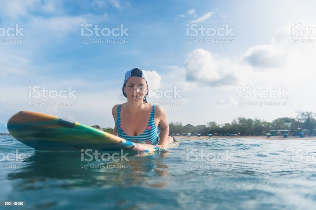 portrait of woman in swimming suit and cap lying on surfing board in ocean - Zbiór zdjęć royalty-free (Bali)