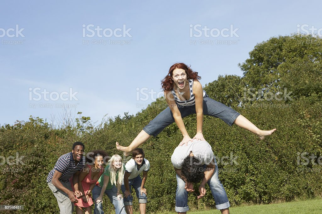Portrait of woman jumping over the top of man royalty free stockfoto