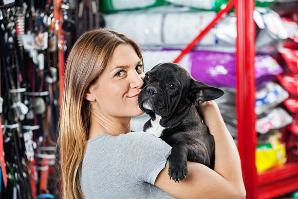Portrait Of Woman Kissing French Bulldog At Store stock photo