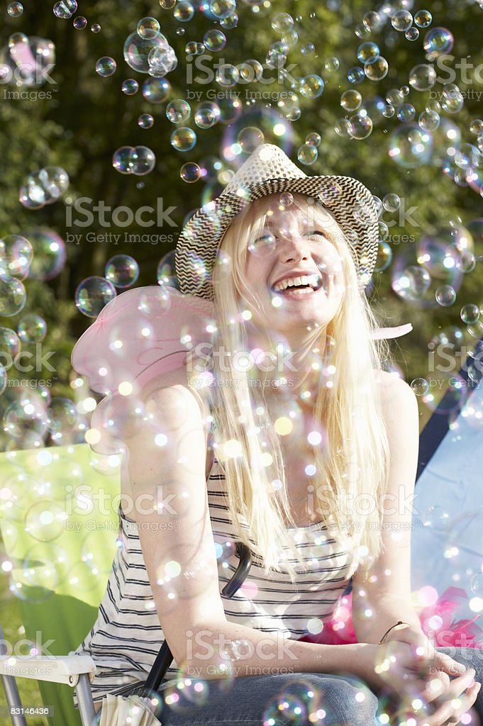 Portrait of woman laughing and looking at bubbles foto stock royalty-free