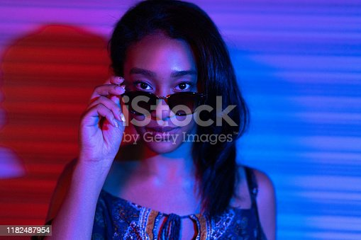 1049378188 istock photo Portrait of woman lit by neon lights at night 1182487954