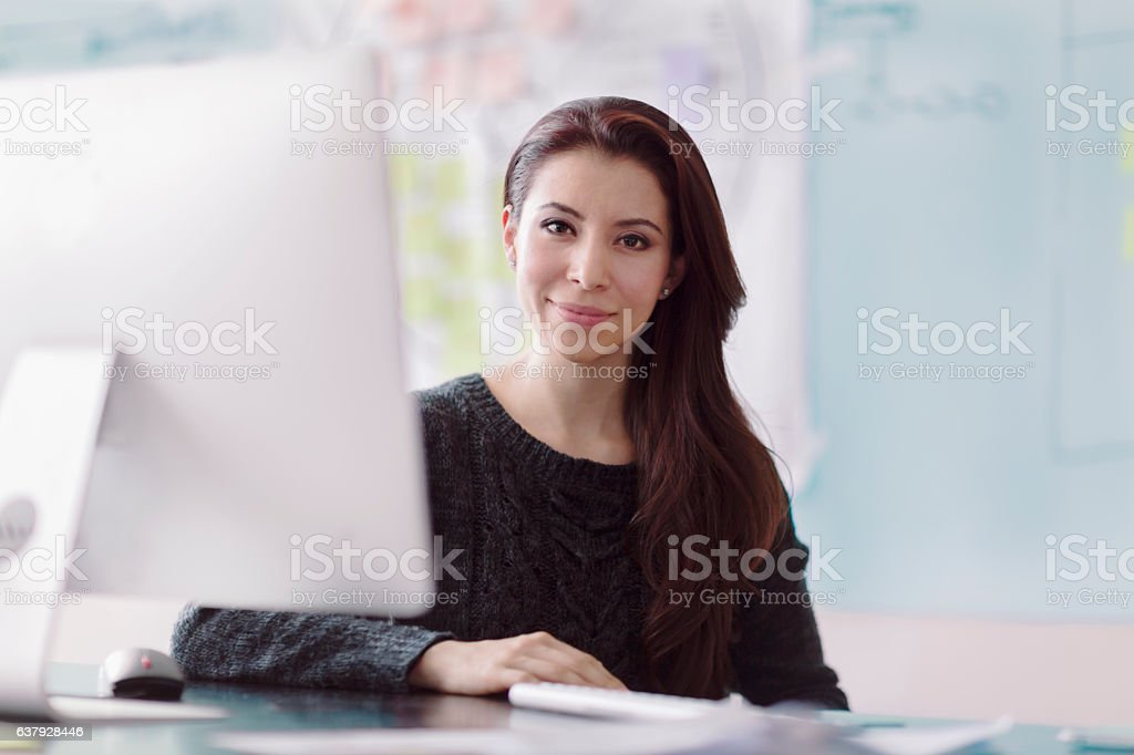 Portrait of woman next to computer in studio office - Photo