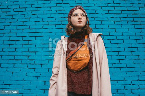 Portrait of  young Caucasian woman on the background of blue wall