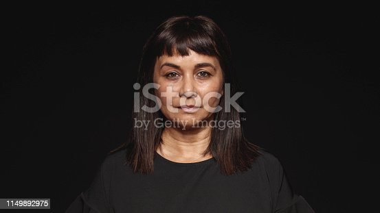 Close up of middle aged woman looking at camera. Woman in  black dress isolated on black background.