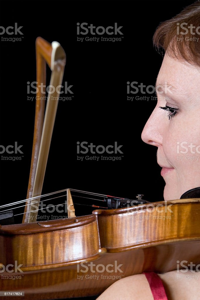 portrait of woman plays the viola on black background stock photo