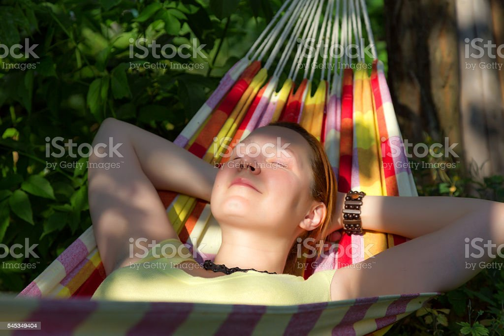 Portrait of Woman relaxing in Hummock at Summer Garden stock photo
