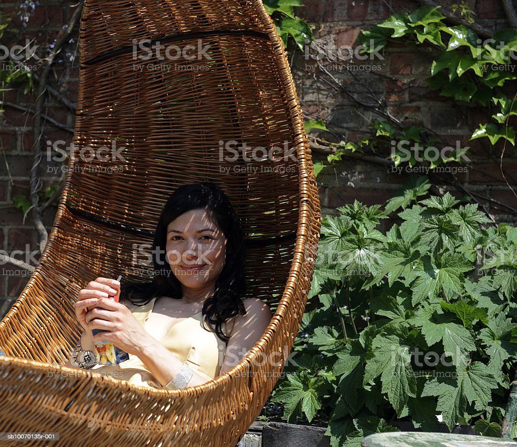 Portrait of woman relaxing in wicker hammock royalty free stockfoto