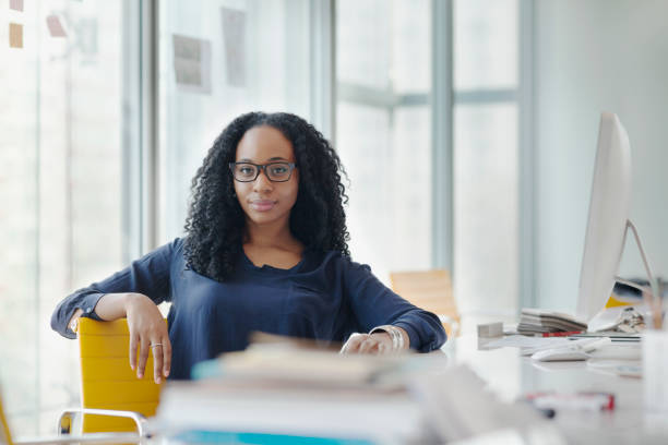 Portrait of woman sitting at desk in design office stock photo