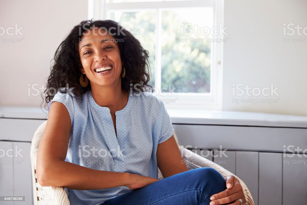 Portrait Of Woman Sitting In Chair At Home stock photo