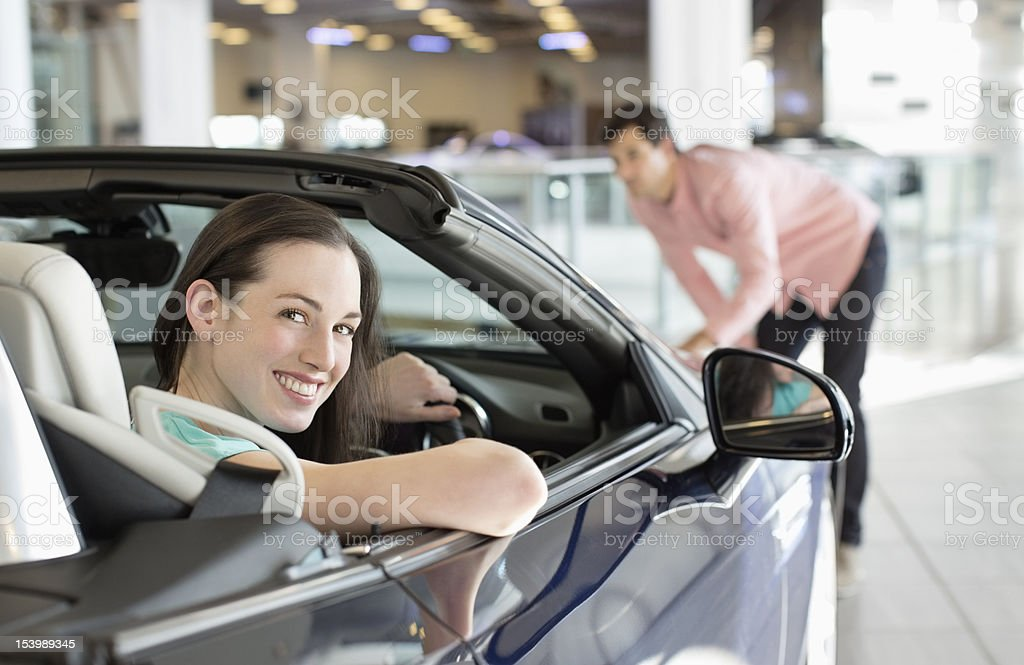 Portrait of woman sitting in convertible in car dealership showroom royalty-free stock photo