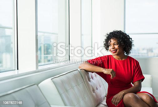 A portrait of happy black woman sitting on a sofa by the window in an office. Copy space.