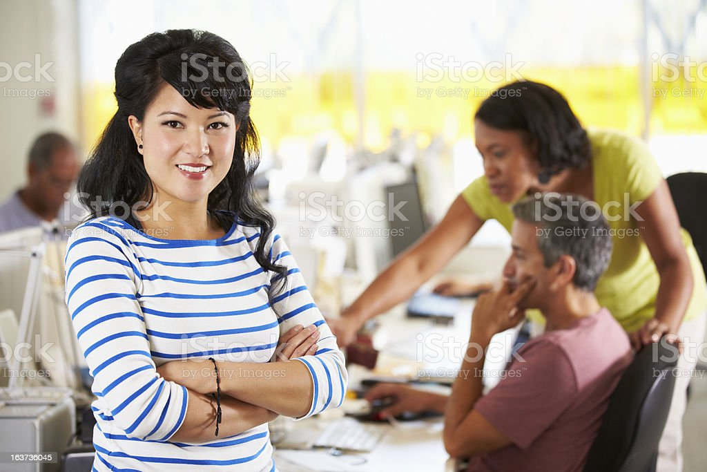 Portrait Of Woman Standing In Busy Creative Office stock photo