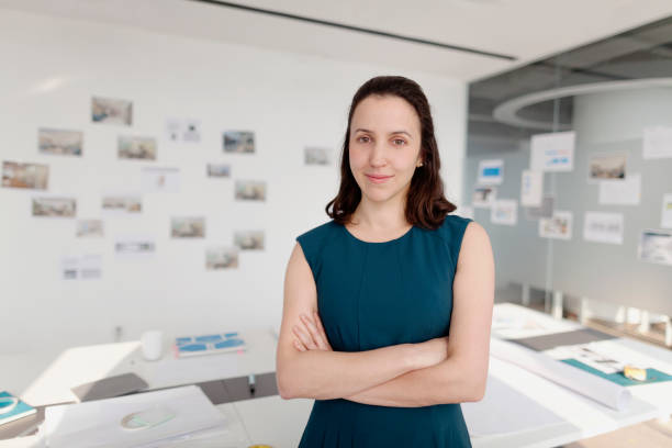 portrait of woman standing in design office with arms crossed - curator stock pictures, royalty-free photos & images