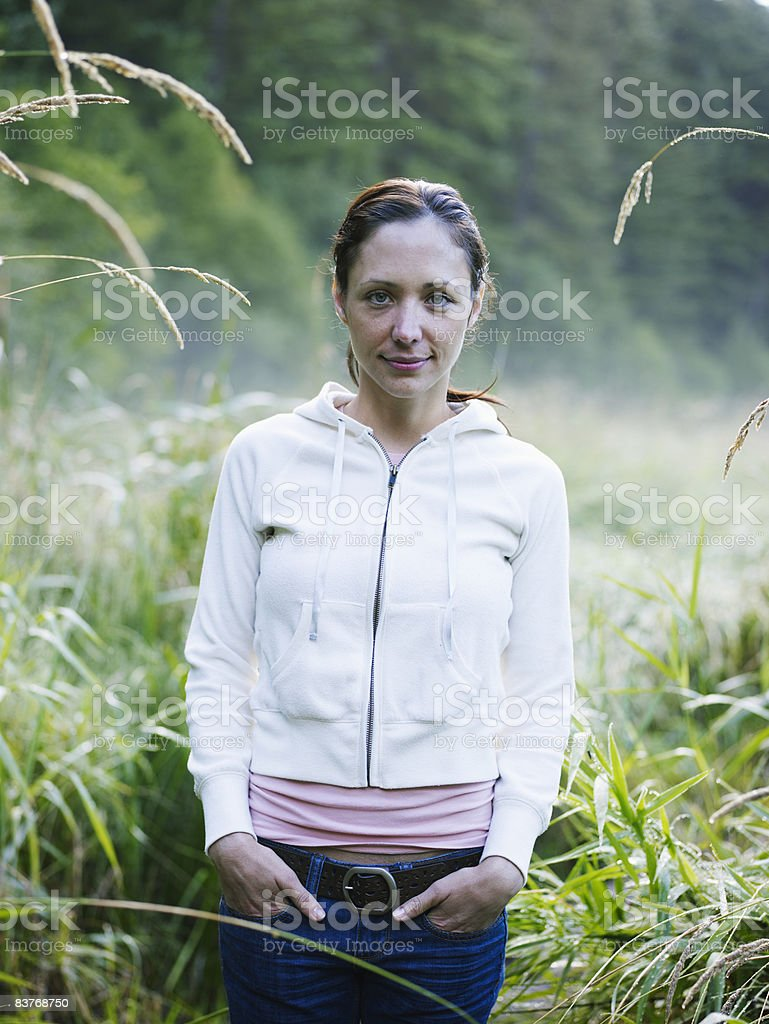 Portrait of woman standing in field, dawn royaltyfri bildbanksbilder