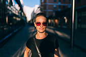 Portrait of woman wearing sunglasses and black shirt standing in the street at sunset with half a face lit by the sunlight and strong shadows